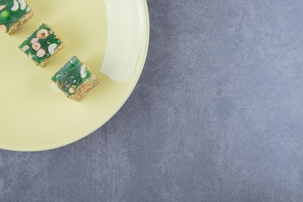 Bovenaanzicht als turks fruit rahat lokum met hazelnoten op gele plaat.