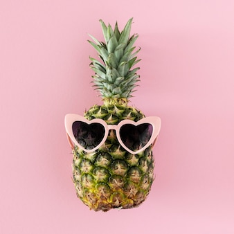 Bovenaanzicht ananas met hartvormige zonnebril