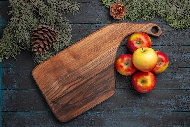 Bovenaanzicht appel en bord vijf geel-roodachtige appels naast de houten snijplank op grijze tafel tussen boomtakken met kegels
