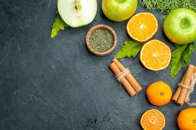 Bovenaanzicht appel- en sinaasappelschijfjes gedroogd muntpoeder in kom kaneelstokjes pijnboomtakken op zwarte tafel met kopieerruimte