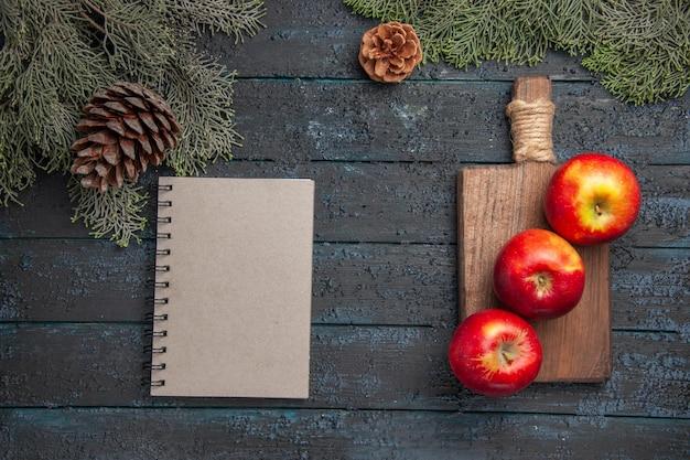 Bovenaanzicht appels aan boord van drie appels op houten snijplank en notebook onder takken met kegels