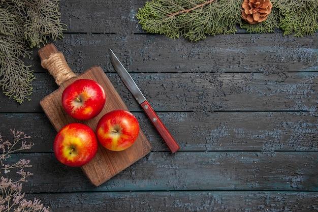 Bovenaanzicht appels aan boord van drie geel-roodachtige appels op de bruine snijplank onder de boombanches met kegels aan de linkerkant van de tafel