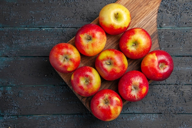 Bovenaanzicht appels aan boord van negen geel-rode appels op een houten snijplank op grijze tafel