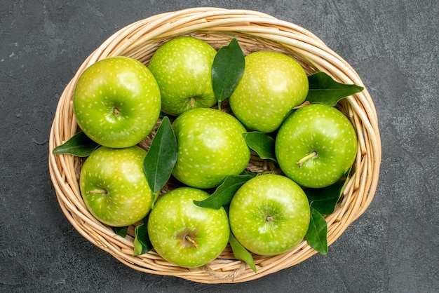 Bovenaanzicht appels in de mand acht appels met groene bladeren in de houten mand