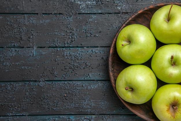 Bovenaanzicht appels op tafel zeven groengele appels in kom aan de rechterkant van donkere tafel