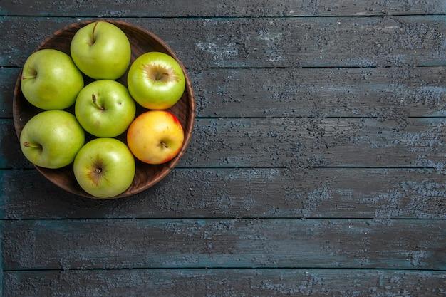 Bovenaanzicht appels op tafelschaal van zeven groen-geel-rode appels aan de linkerkant van donkere tafel
