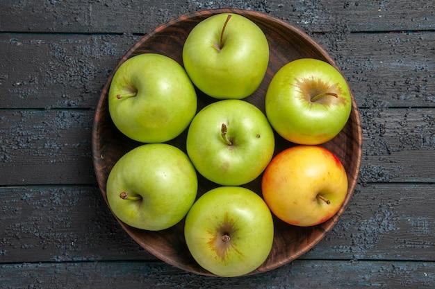 Bovenaanzicht appels op tafelschaal van zeven groen-geel-rode appels op donkere tafel