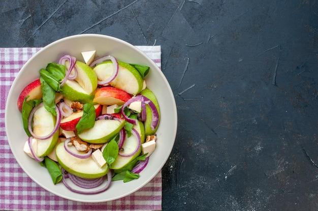 Bovenaanzicht appelsalade in kom paars en wit geruit servet op donkere tafel met kopieerplaats