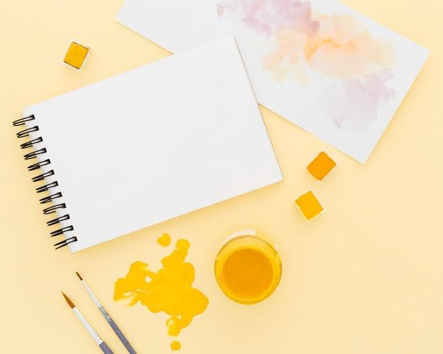 Bovenaanzicht aquarel met kladblok op tafel