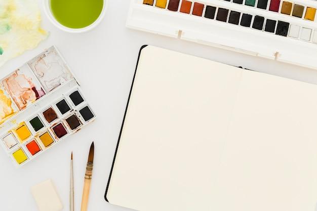 Bovenaanzicht aquarellen met penselen op tafel