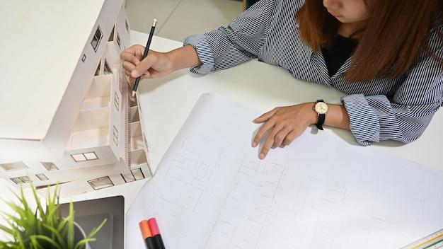 Bovenaanzicht architect werken met model huis en blauwdruk in een kantoor aan huis.