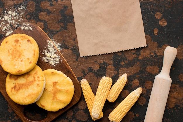 Bovenaanzicht arepas op houten bord en maïs