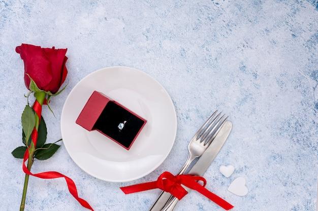Bovenaanzicht arrangement met bloem en verlovingsring