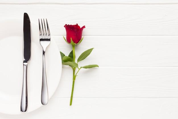 Bovenaanzicht arrangement met bord, bestek en roos