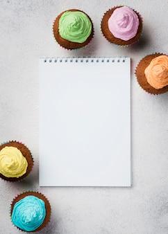 Bovenaanzicht arrangement met geglazuurde muffins en notebook