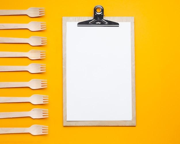 Bovenaanzicht arrangement met klembord en vorken