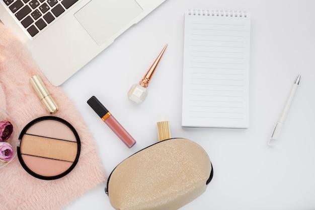 Bovenaanzicht arrangement met make-up artikelen en laptop
