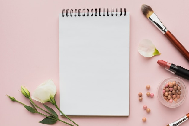 Bovenaanzicht arrangement met make-up producten en notebook