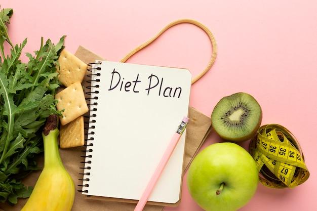 Bovenaanzicht arrangement met notitieblok voor dieetplanning
