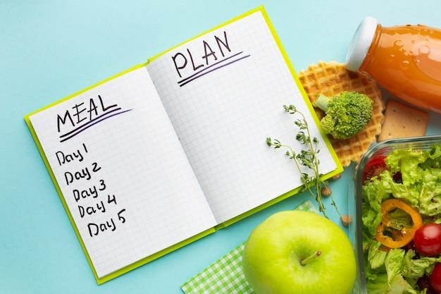 Bovenaanzicht arrangement met notitieboek voor maaltijdplanning
