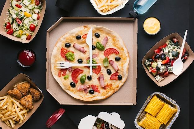 Bovenaanzicht arrangement met pizzadoos en salades