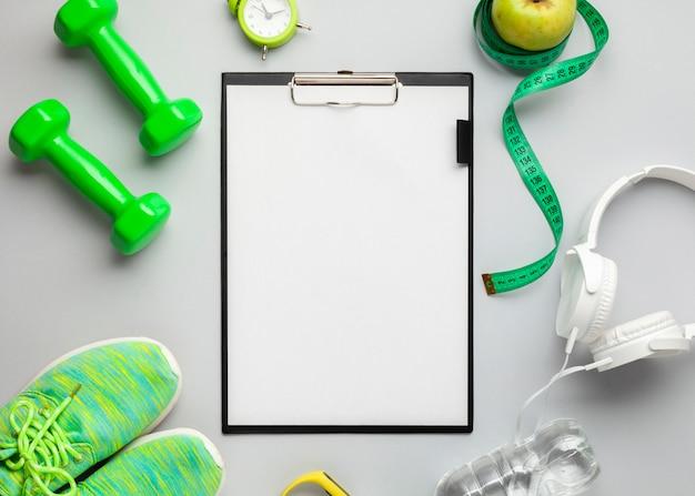 Bovenaanzicht arrangement met sportattributen en klembord
