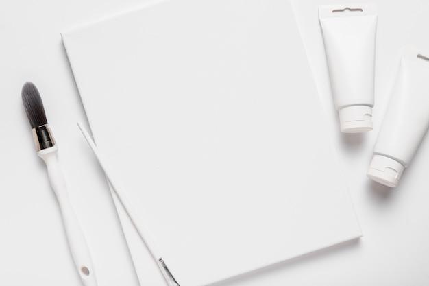 Bovenaanzicht arrangement met stuk papier en penseel