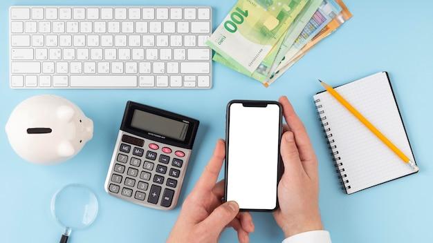 Bovenaanzicht arrangement van economie-elementen met lege smartphone