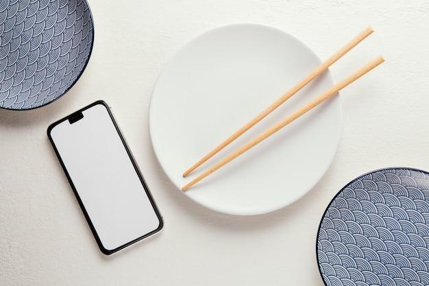 Bovenaanzicht arrangement van elegant serviesgoed met smartphone
