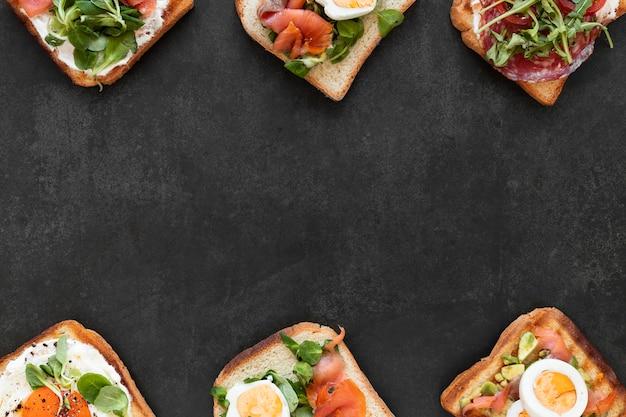 Bovenaanzicht arrangement van heerlijke broodjes op zwarte achtergrond met kopie ruimte