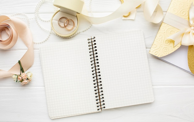 Bovenaanzicht arrangement van lege notebook en trouwringen