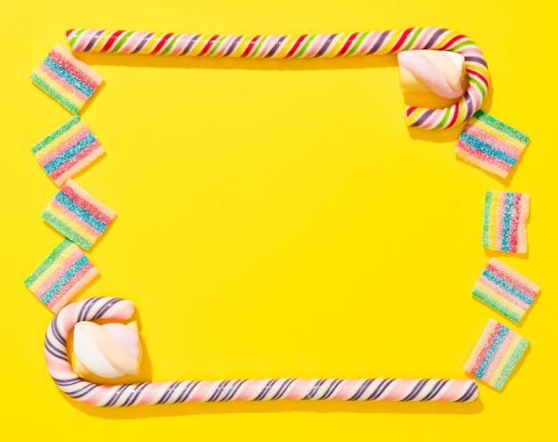 Bovenaanzicht arrangement van snoepjes op gele achtergrond met kopie ruimte