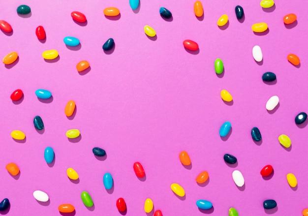 Bovenaanzicht arrangement van verschillende gekleurde snoepjes op roze achtergrond met kopie ruimte