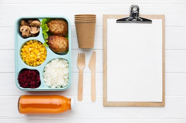 Bovenaanzicht arrangement van verschillende voedingsmiddelen met leeg klembord
