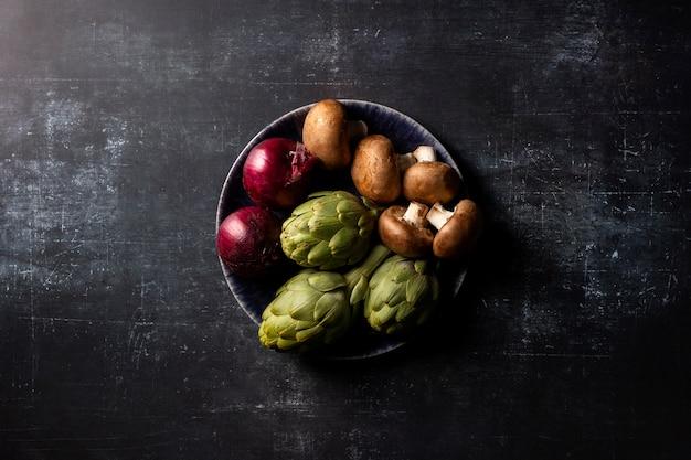 Bovenaanzicht artisjok met rode uien en champignons in kom