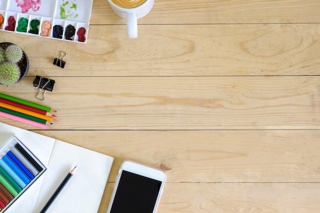 Bovenaanzicht artist werkruimte smartphone, kleur, mok koffie, kladblok papier, cactus en potlood op houten tafel
