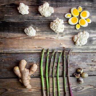 Bovenaanzicht asperges met gember, eieren, bloemkool op donkere houten achtergrond.