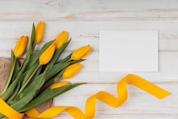 Bovenaanzicht assortiment gele tulpen met lege kaart