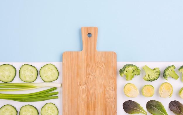 Bovenaanzicht assortiment groenten met snijplank