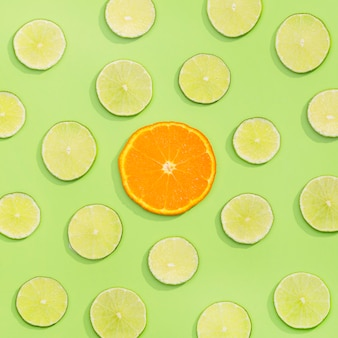 Bovenaanzicht assortiment van biologische limoen en stukjes sinaasappel