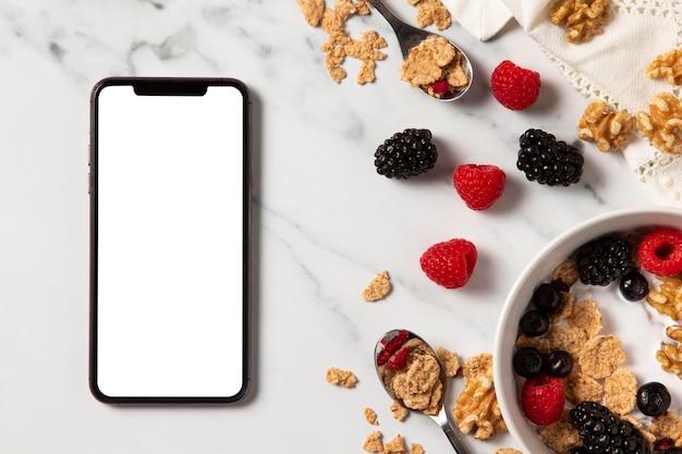 Bovenaanzicht assortiment van gezonde komgranen met lege scherm smartphone