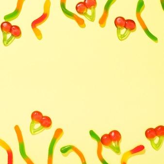 Bovenaanzicht assortiment van kleurrijke snoepjes op gele achtergrond met kopie ruimte