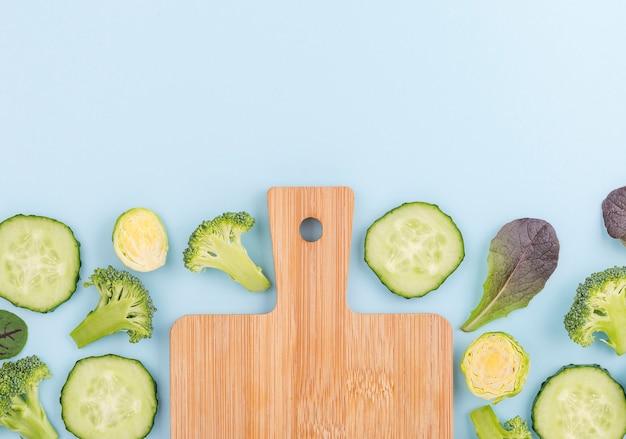 Bovenaanzicht assortiment van komkommer plakjes met snijplank