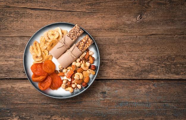 Bovenaanzicht assortiment van noten en gedroogde vruchten met melk in een kom op een houten ondergrond