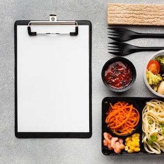 Bovenaanzicht assortiment van verschillende voedingsmiddelen met leeg klembord