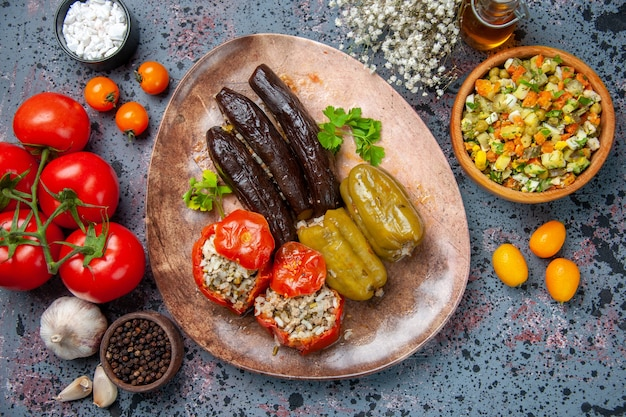 Bovenaanzicht aubergine dolma met gekookte tomaten en paprika gevuld met gehakt in plaat, schotel diner voedsel maaltijd kleur