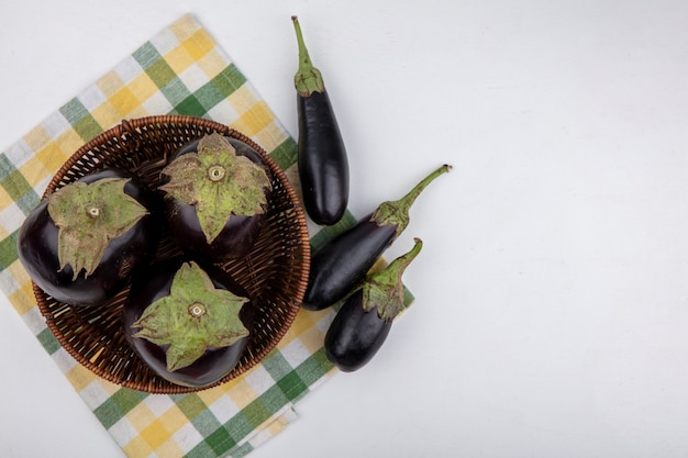Bovenaanzicht aubergine in een mand op een gele geruite handdoek op een witte achtergrond