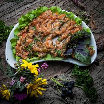 Bovenaanzicht aubergine kaviaar met sla, basilicum in een witte plaat