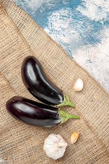 Bovenaanzicht aubergines knoflook op stro tafelkleed op blauw-wit oppervlak