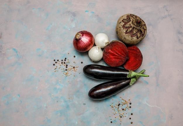 Bovenaanzicht aubergines met rode biet, uien op gestructureerd oppervlak. horizontale vrije ruimte voor uw tekst